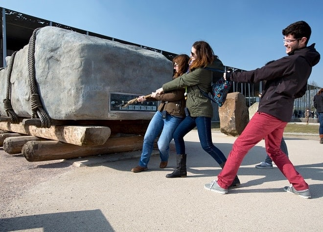 a group of visitors to stonehenge try and pull a sarsen megalith