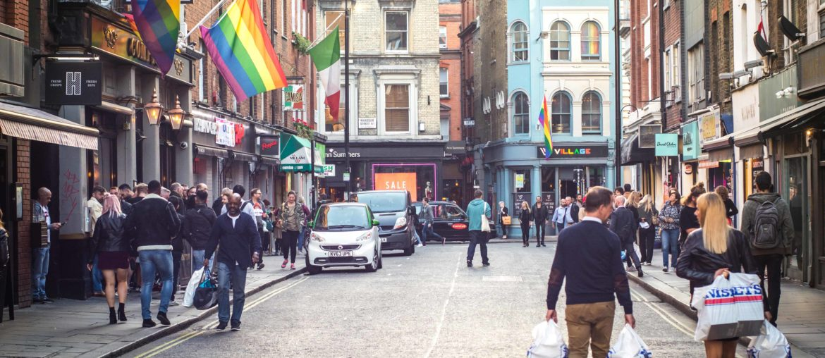 Shoppers walking down a Soho street in London's westend past a bar with a LGBT rainbow flag