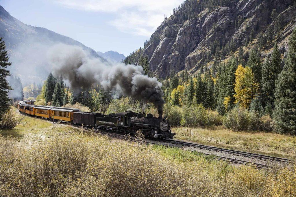 locomotive steam engine passing through mountain pass